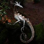 A polished stainless steel and bronze dragon